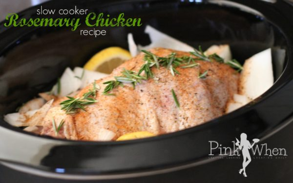 Slow Cooker Rosemary Whole Chicken in a crockpot with seasonings and rosemary on top with lemon and onion surrounding the sides.