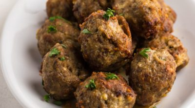 Italian Meatballs stacked on a plate for serving.