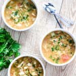 red lentil soup on wood table with spoon