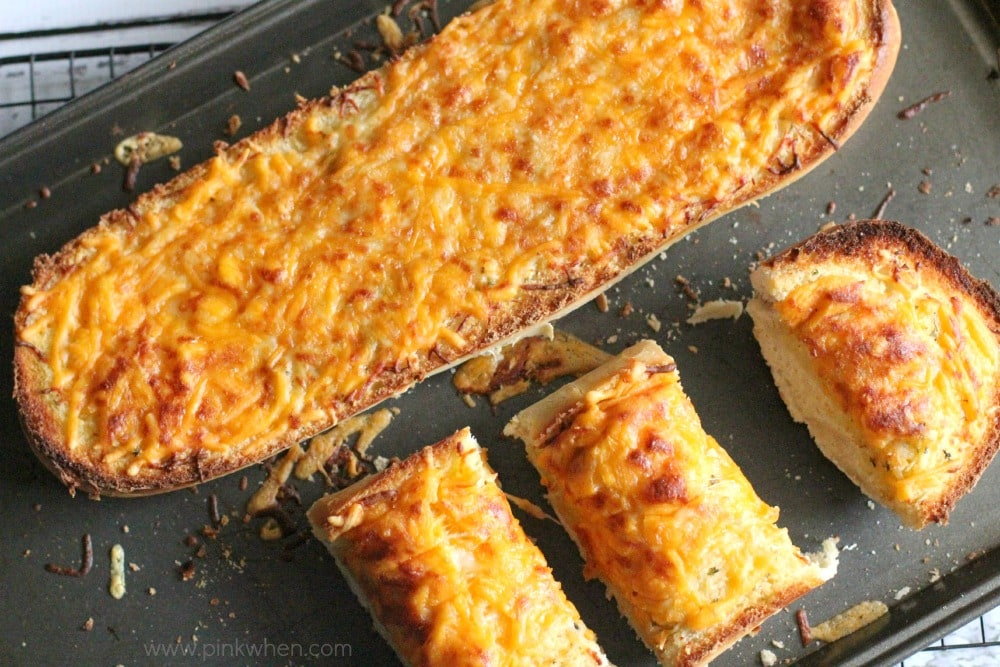 Garlic cheese bread sliced and on a cookie sheet.