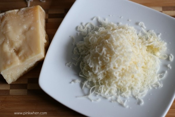 Shredded cheese on a white plate.