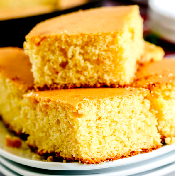 Skillet cornbread cut and stacked on a white plate.