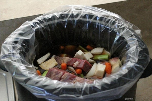 Vegetables and Meat in a liner for a Slow Cooker Pot Roast.