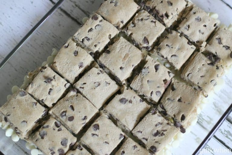 cookie dough squares placed on top of white chocolate chips in a baking dish.