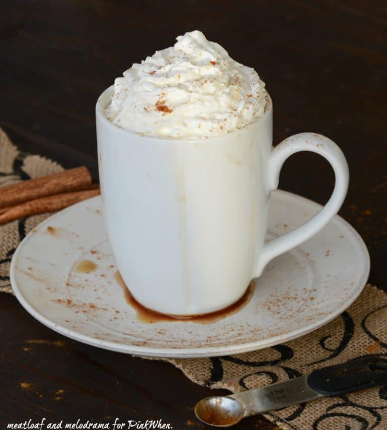 cinnamon-vanilla-with whipped cream in a white cup on a white plate.