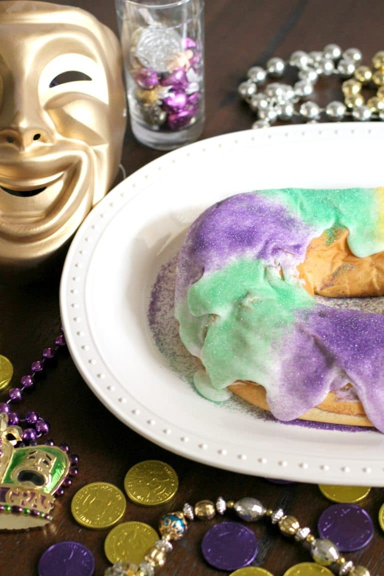 King cake on a white plate with a mardi gras mask and beads in the background.