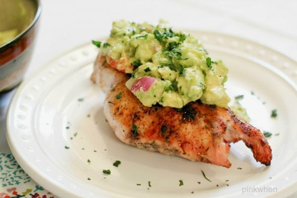 grilled chicken with avocado salsa on a white plate