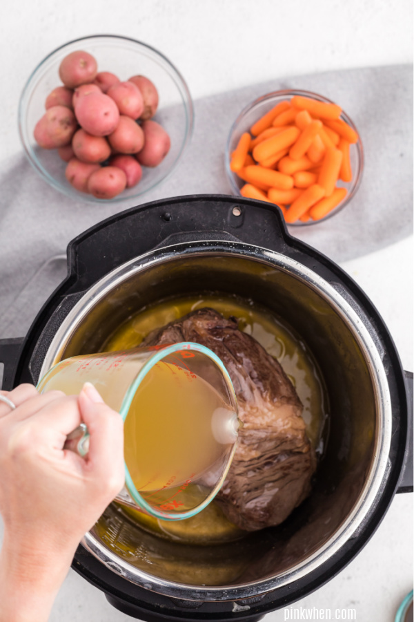 Pouring broth into the pressure cooker.