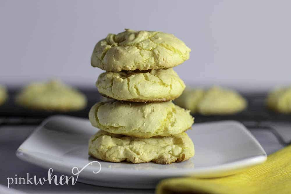 4 Lemon Cake Mix Cookies stacked on a square white plate.