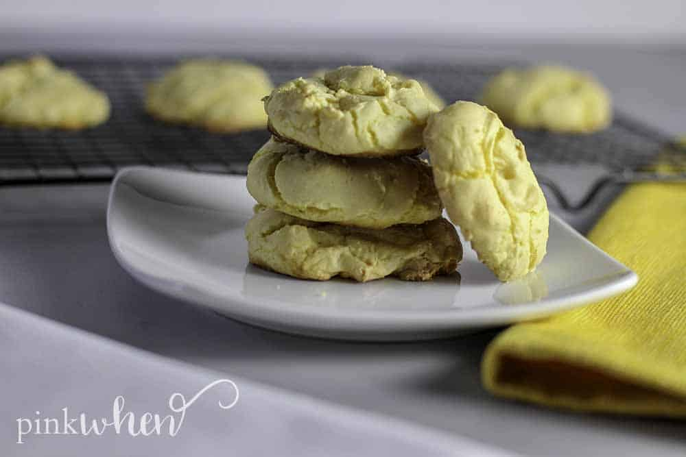 Lemon Cake Mix Cookies stacked on a white plate with cookies cooling in the background on a wire rack.