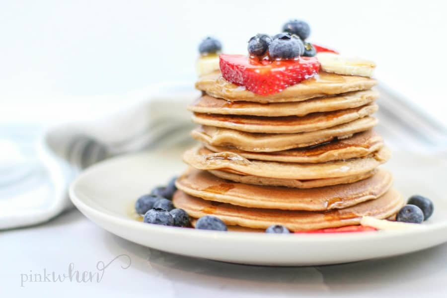 Protein pancakes covered in fruit on a white plate.