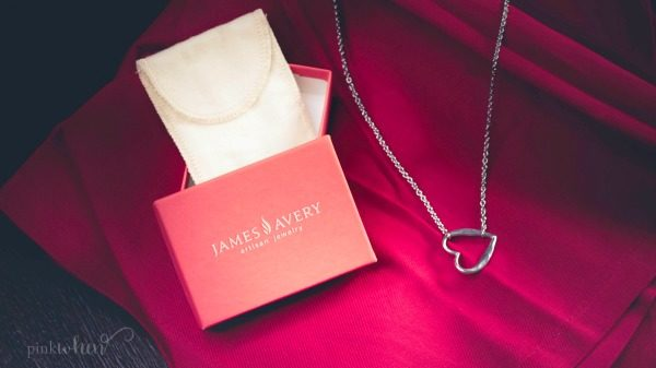 A James Avery Jewelry box with heart necklace on red cloth.