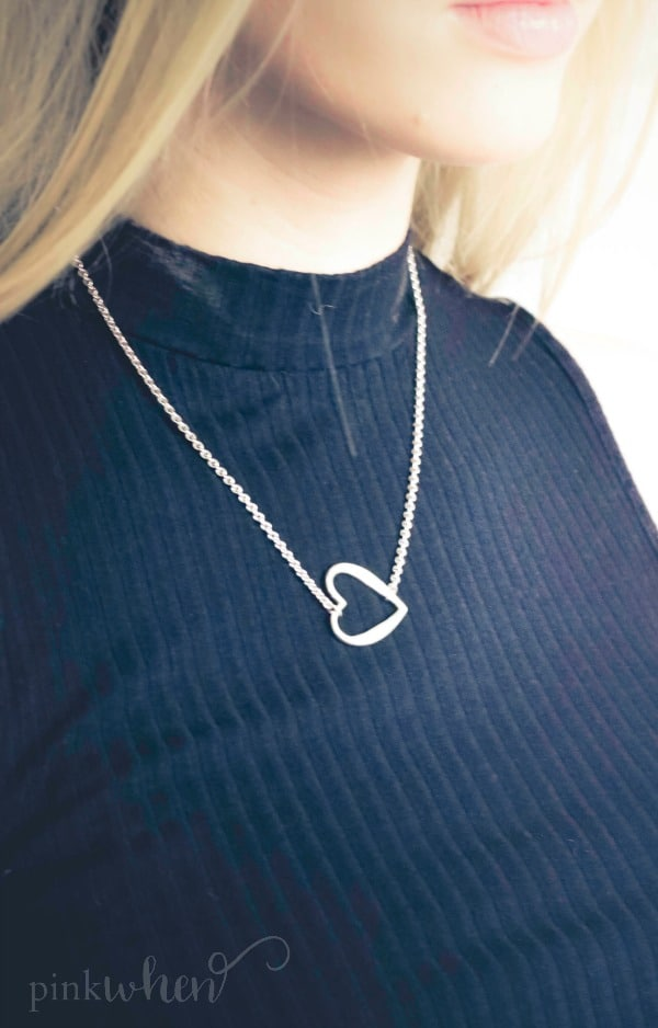 heart shaped necklace on girl dressed in a black shirt