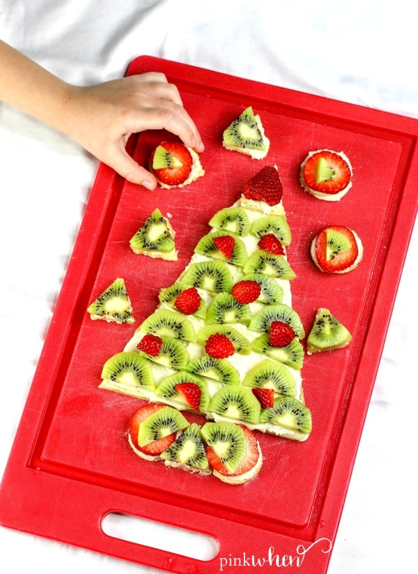 Christmas Fruit Pizza is covered in cream cheese frosting shaped like a Christmas tree on a red cutting board. A little hand is trying to sneak a cookie.