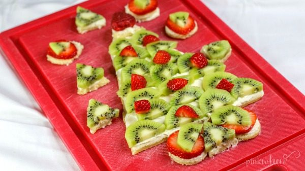 Christmas Fruit Pizza in the shape of a Christmas tree covered in cream cheese frosting and fruit on a red cutting board.