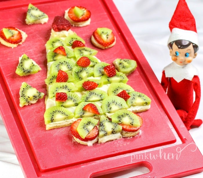 Christmas Fruit Pizza with cream cheese frosting and covered in fruit on a red cutting board with an elf looking on.