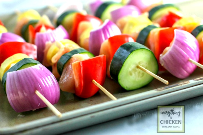 Chicken and vegetables on skewers lined up on a tray.