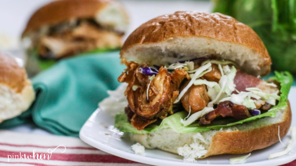 Shredded Slow Cooker BBQ Chicken served on a bun with toppings.