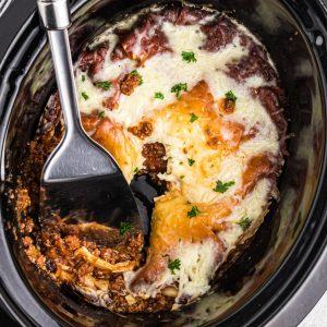 Lasagna in a crockpot ready to serve.