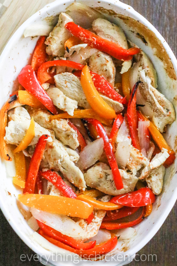 Oven baked chicken fajitas and peppers in a white baking dish.