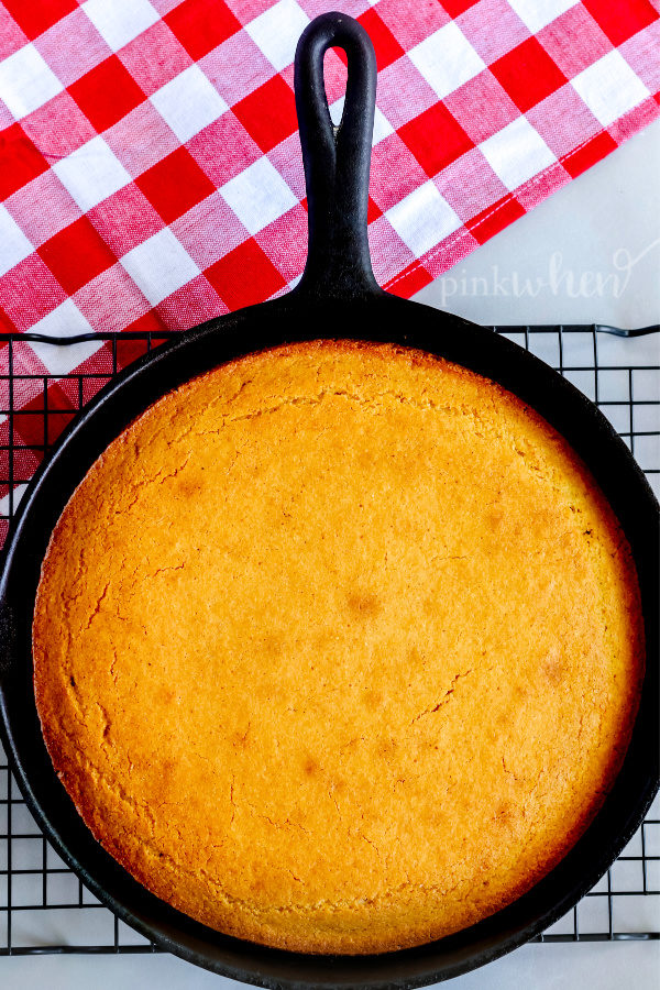 Cornbread cooling in a skillet on a wire rack.