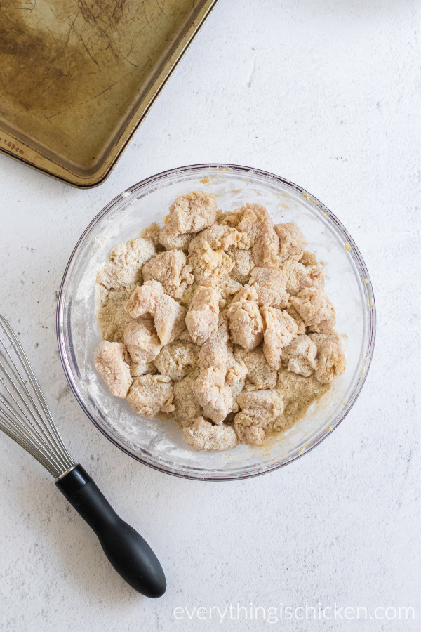 chicken nuggets dredged in flour mixture ready to fry.