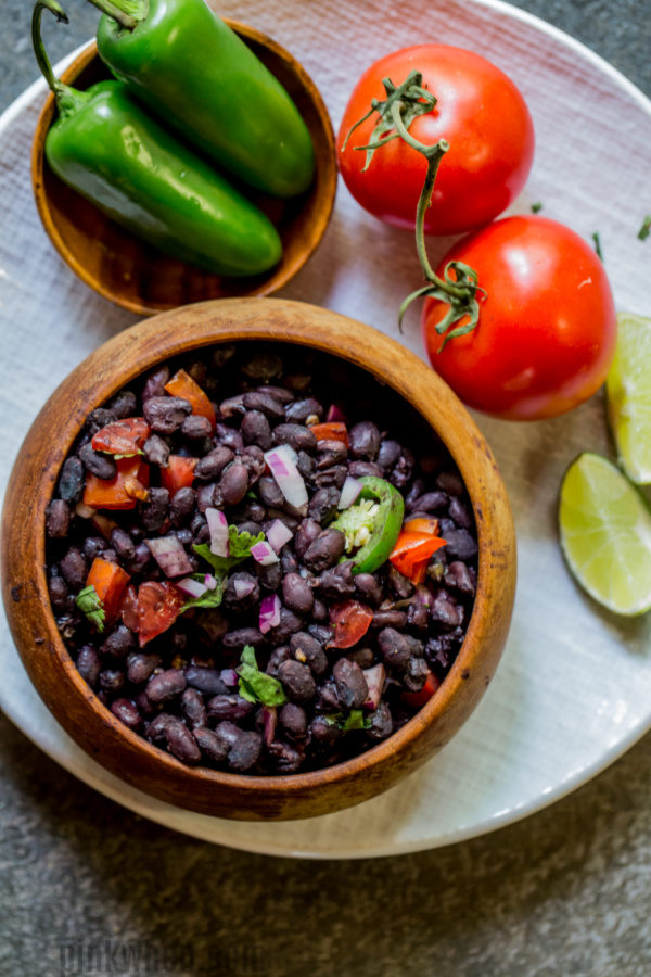 Black beans in a bowl with jalapeno and tomato on a plate.