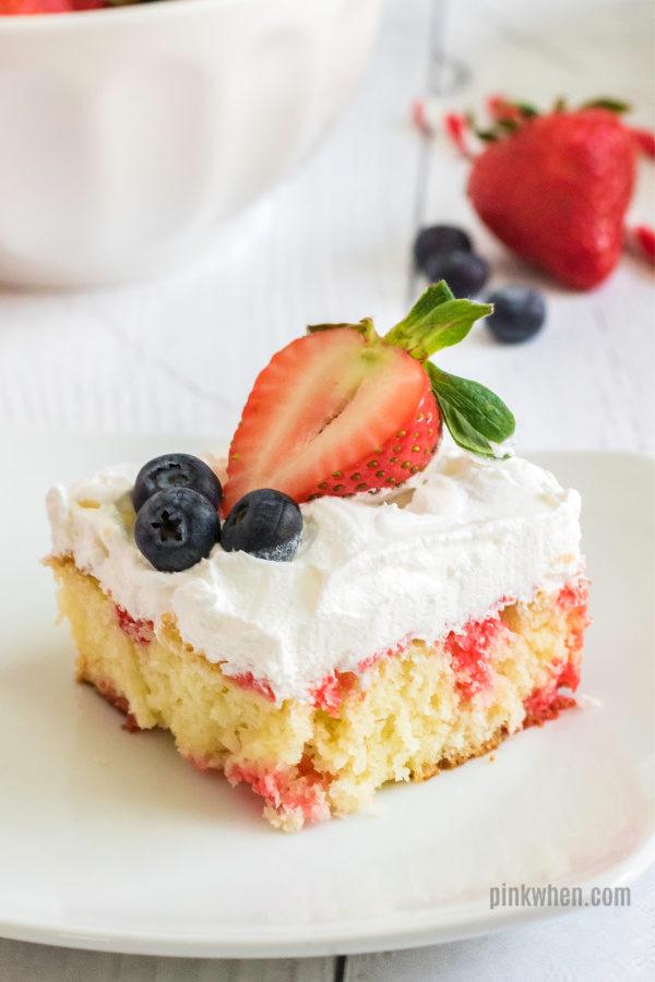 strawberry poke cake on a white plate ready to serve.
