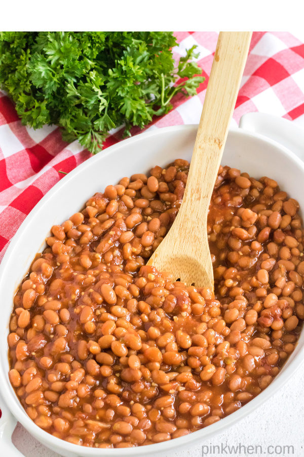 Baked beans with a wooden spoon.