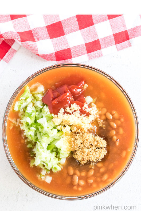 Ingredients in a bowl being used to create baked beans.