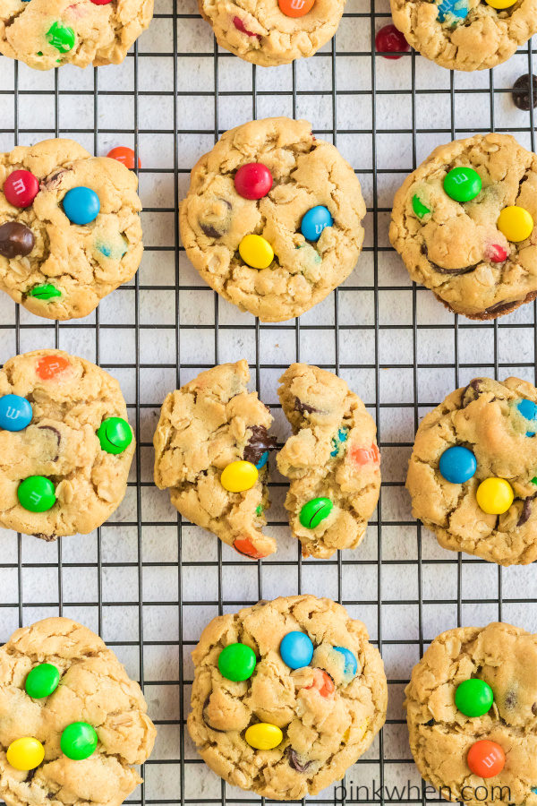 Monster cookies on a cookie rack with a broken cookie in the middle.