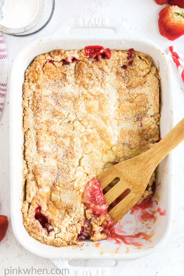 Strawberry dump cake with a scoop missing.