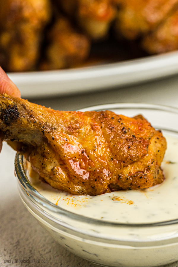 Air Fryer Chicken Wing dipping in ranch dressing.