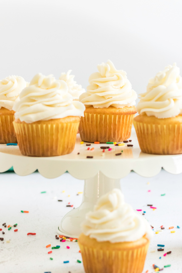 Buttercream frosted cupcakes on a cake stand.