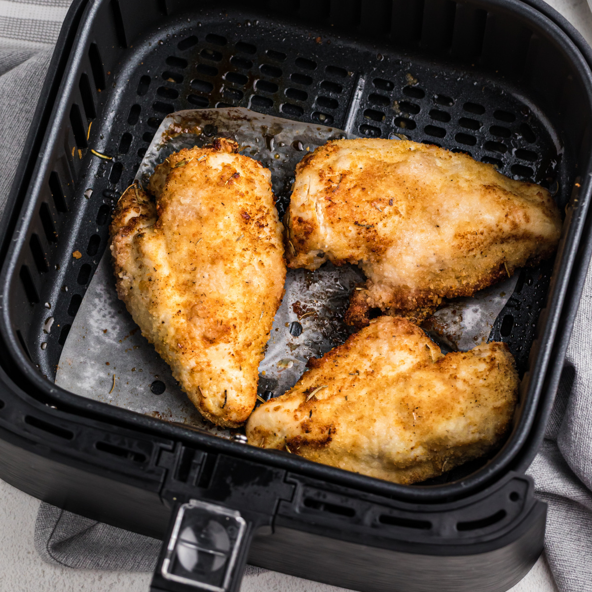 Air Fryer Chicken breast fully cooked in a basket.