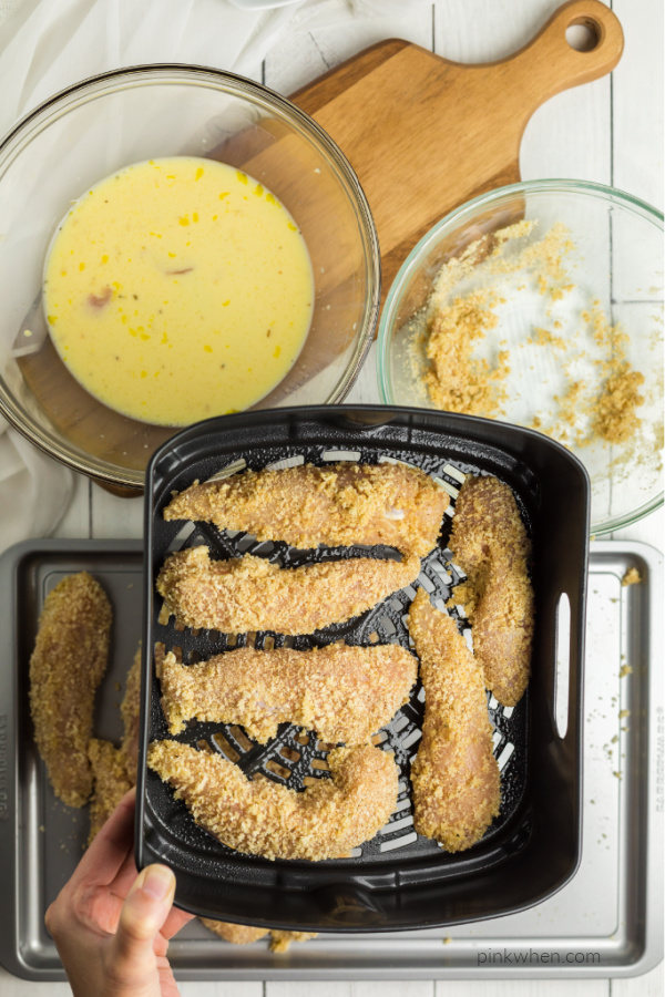 breaded chicken strips in an air fryer basket.