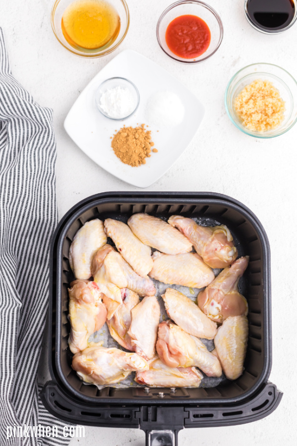 Wings in an air fryer basket ready to cook.