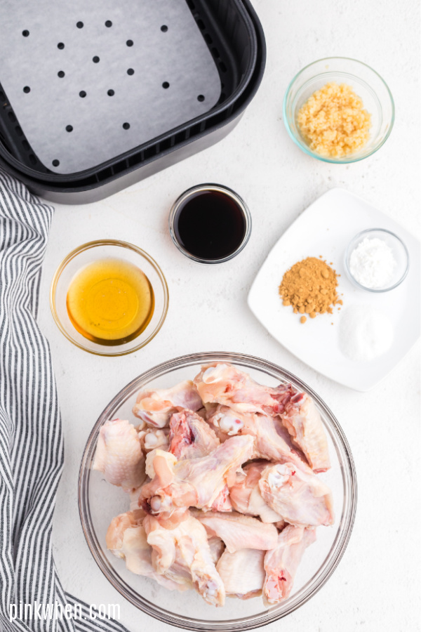 Air Fryer basket and ingredients needed for chicken wings on a white table.