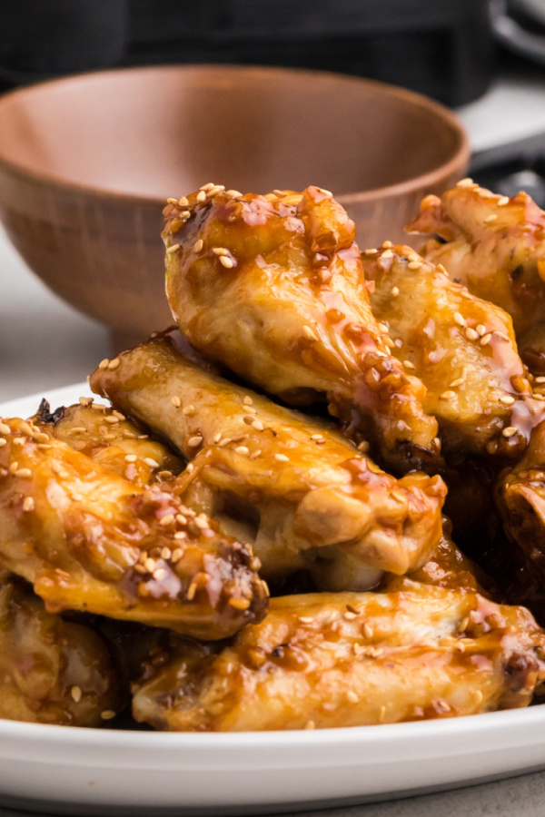 Honey Garlic Wings stacked on a white plate.