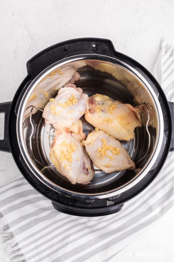 chicken thighs with garlic and set on a trivet in the Instant Pot.