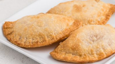Apple hand pies on a white plate.