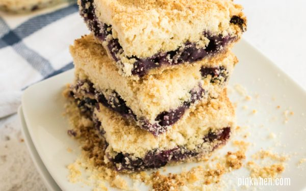 Blueberry crumb bars stacked on a plate.