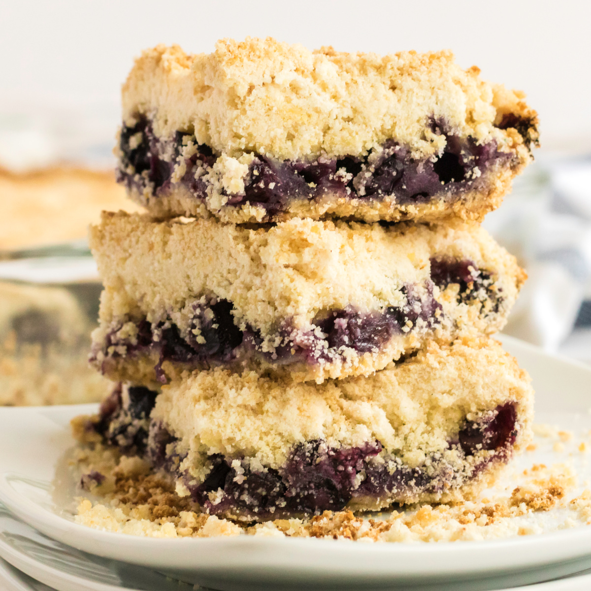 Blueberry crumb bars stacked on a plate and ready to eat.