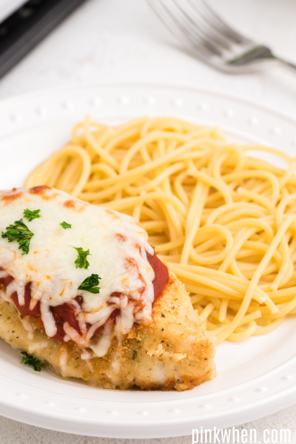Oven baked chicken parmesan with noodles on a white plate.