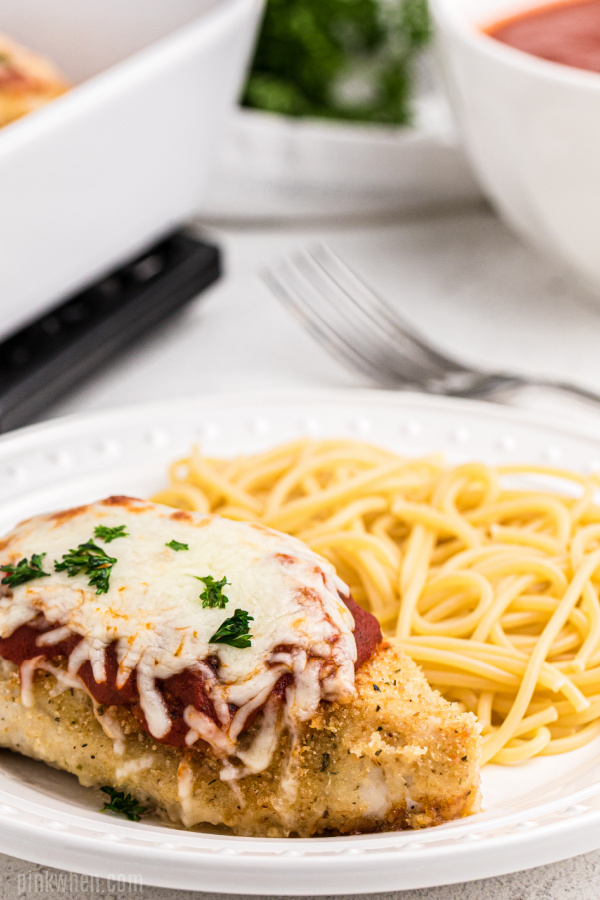 oven baked chicken parmesan on a plate with noodles.