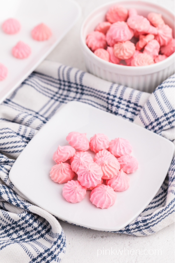 Pink meringue cookies on a white plate ready to serve.