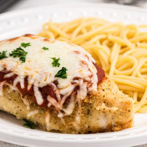 Oven baked chicken parmesan on a plate with noodles