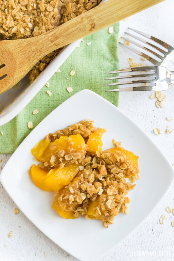 Peach crisp scooped out onto a white plate.
