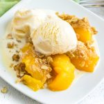 Peach crisp on a white plate with melted ice cream.