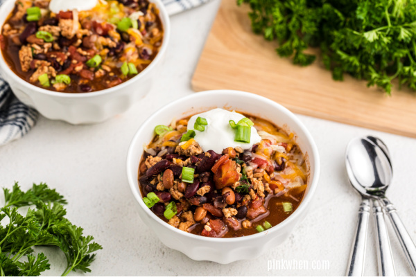 Turkey chili from the crockpot in a white bowl and served with toppings.